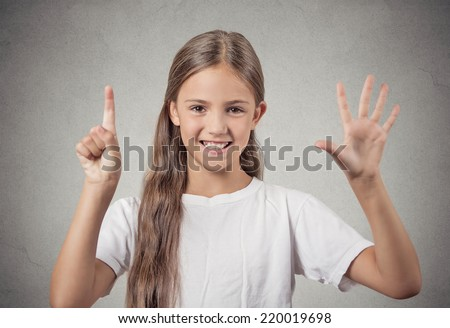 Closeup portrait excited happy teenager girl showing 6 fingers, giving number six sign, isolated grey background. Positive human emotion face expression, attitude, reaction, perception body language - stock photo