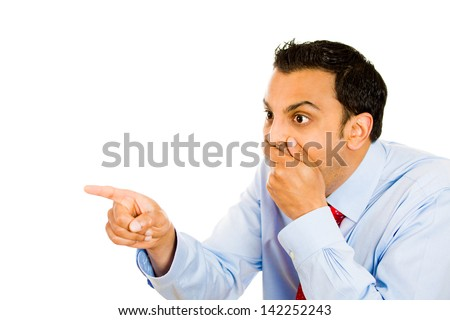 Closeup portrait, excited happy young man pointing away, covering mouth, laughing at someone or something, isolated white background. Negative human emotion facial expression feelings, reaction