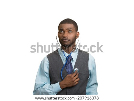 Closeup portrait executive man, business person, worker listening to his heart with stethoscope looking up isolated white background. Preventive medicine, financial condition concept. Face expression - stock photo