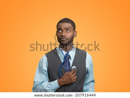 Closeup portrait executive man, business person, worker listening to his heart with stethoscope looking up isolated orange background. Preventive medicine, financial condition concept. Face expression - stock photo