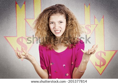 Closeup portrait frustrated, funny looking little girl, hands out, stressed, market, dollar going down, isolated dark, grey background with arrows. Facial expressions, emotions. Future economy worries - stock photo