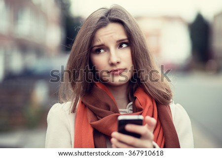 Closeup portrait funny sad young girl looking up thinking seeing bad news sms comment trolling message photos phone in hands disgusting emotion on face isolated cityscape background. Human expression - stock photo