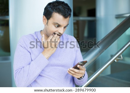Closeup portrait, funny young man, shocked surprised, biting fingernails, by what he sees on his cell phone, isolated indoors office background. Negative human emotions, facial expression feeling - stock photo