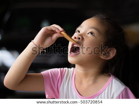 closeup portrait,girl eating a cookie,food,girl holding cookie