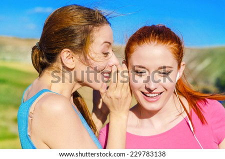Closeup portrait girl whispering into woman ear telling her something secret latest gossip slander, shocked surprised happy response isolated outside background. Human emotion face expression feeling - stock photo