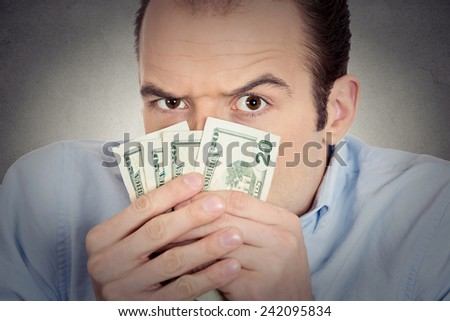 Closeup portrait greedy banker executive CEO boss, corporate employee funny looking man holding dollar banknotes scared to loose money, suspicious isolated grey background. Human face expression - stock photo