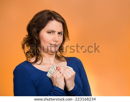 Closeup portrait greedy middle aged woman corporate business employee, worker, student holding dollar banknotes tightly isolated orange background. Negative human emotion facial expression feeling - stock photo