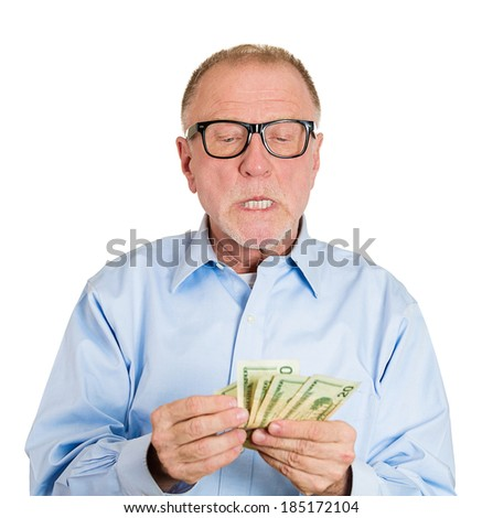 Closeup portrait, greedy, nerd senior executive, CEO, boss, old corporate employee, mature man, counting dollar banknotes carefully, isolated white background. Negative human emotion facial expression - stock photo