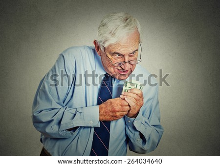 Closeup portrait greedy senior executive, CEO, boss, old corporate employee, mature man, holding dollar banknotes isolated on gray wall background. Negative human emotion facial expression  - stock photo