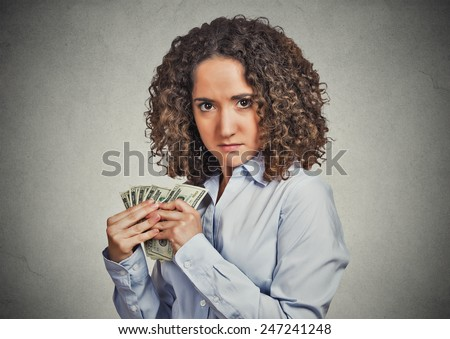 Closeup portrait greedy young woman corporate business employee, worker, student holding dollar banknotes tightly isolated grey wall background. Negative human emotion facial expression feeling - stock photo