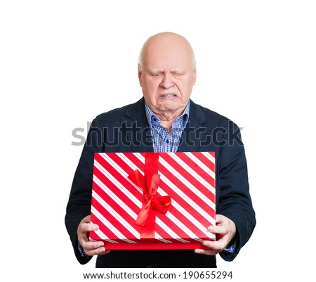 Closeup portrait grumpy, upset senior man holding gift box, very displeased with what he received, disgust on face isolated white background. Negative human emotion, facial expression feeling attitude