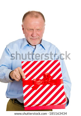 Closeup portrait grumpy, upset senior mature man holding gift box, very displeased with what he received, disgust on face isolated white background. Negative emotion facial expression feeling attitude