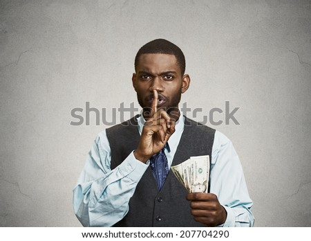 Closeup portrait handsome corrupt guy businessman holding dollar bill in hand showing shhh sign finger to lips isolated grey background. Bribery concept politics, business diplomacy. Face expression - stock photo
