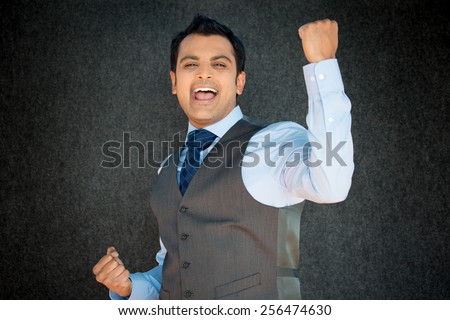 Closeup portrait, handsome excited, energetic, happy, smiling student man winning, arms, fists pumped, celebrating success, isolated gray black background. Positive emotion, facial expressions - stock photo