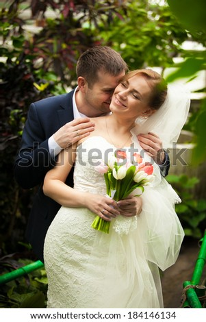 Closeup portrait handsome groom kissing bride in neck at jungle