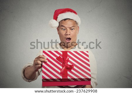 Closeup portrait handsome middle aged man wearing red santa claus hat opening gift box surprised happy at what he gets isolated grey wall background. Positive human emotion facial expression feeling - stock photo