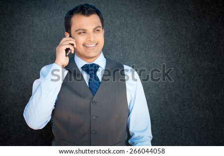 Closeup portrait, handsome young business man, happy guy, in vest and tie, using cell phone, smiling, having pleasant conversation, isolated gray black background. Human emotions, expression - stock photo