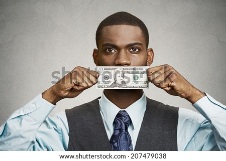 Closeup portrait handsome young corrupt corporate man in blue shirt holding twenty dollar bill to mouth, isolated grey background. Bribery concept in politics, business, diplomacy. Life perception - stock photo