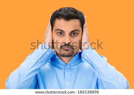 Closeup portrait, handsome young man covering, closing his ears with hands, eyes observing, closed mouth, isolated orange background. Hear no evil concept. Human emotion, facial expression - stock photo