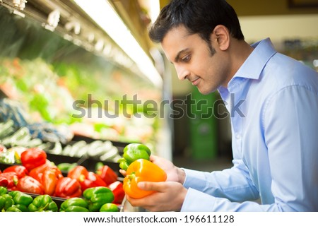 Closeup portrait, handsome young man in blue shirt picking up bell peppers, choosing yellow and orange vegetables in grocery store - stock photo