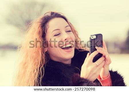 Closeup portrait, happy, cheerful, girl, excited by what she sees on cell phone, isolated background outdoors park. Facial expression, reaction. Beautiful woman sending text message from her mobile - stock photo