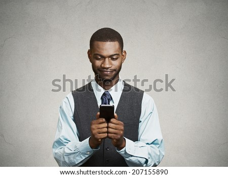 Closeup portrait happy cheerful, young adult business man, excited by what he sees on his cell phone isolated black background. Positive human emotion facial expression, feeling reaction body language - stock photo