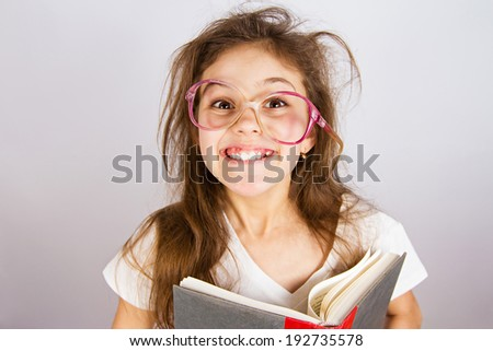 Closeup portrait happy, excited, smiling, funny looking little girl with glasses, holding book, discovered something new, isolated grey blackboard. Human facial expression, emotion, feeling, reaction - stock photo