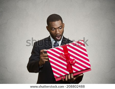 Closeup portrait happy excited surprised young businessman about to open unwrap red gift box isolated grey background, enjoying his present. Positive human emotions, facial expression feeling attitude - stock photo
