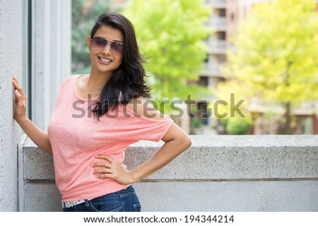 Closeup portrait, happy, gorgeous, beautiful, smiling young woman in pink shirt, sunglasses, posing on outdoors balcony, isolated on background with trees, and buildings, city urban life - stock photo