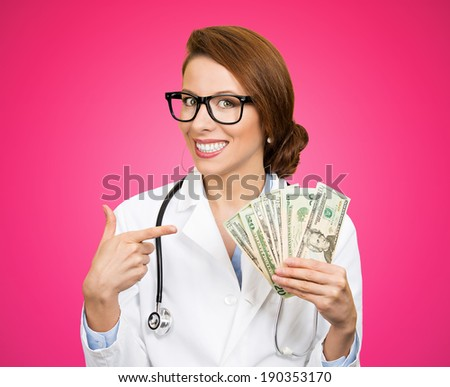 Closeup portrait, happy, health care professional, business woman, doctor holding dollar bills, cash, money in hand, isolated pink background. Human emotions, facial expressions, attitude, finances - stock photo
