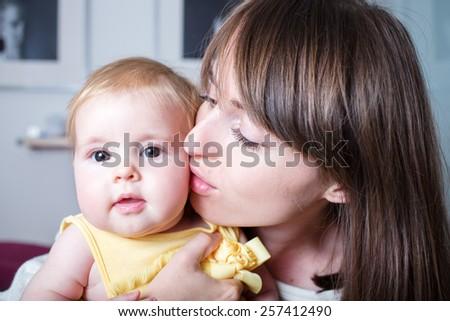 Closeup portrait happy mom gently kissing joyful baby - stock photo