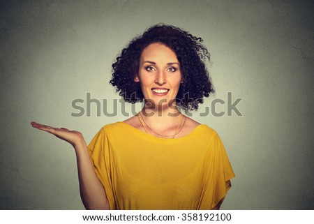 Closeup portrait happy pretty confident young smiling woman gesturing presenting space at left with palm up isolated gray background. Positive human emotion signs symbol, facial expression feelings - stock photo