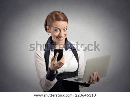 Closeup portrait happy shocked surprised business woman corporate executive reading news on smart mobile cell phone holding laptop computer isolated grey background. Human face expression emotion  - stock photo