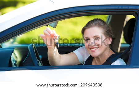 Closeup portrait happy, smiling, attractive woman, buyer sitting in her new white car showing keys isolated outdoors street dealership lot background. Personal transportation, auto purchase concept - stock photo