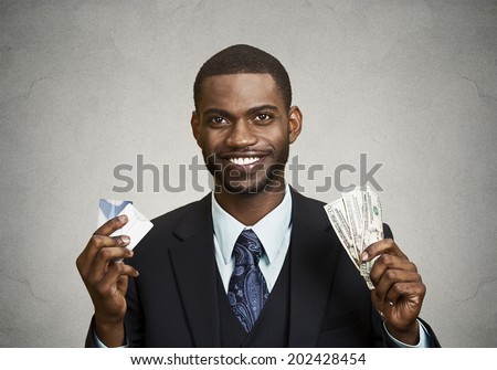 Closeup portrait happy, smiling business man company employee standing, holding dollar bills, credit card hand isolated grey black background. Banking exchange rate concept. Facial expression reaction - stock photo
