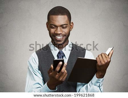 Closeup portrait happy, smiling business man, executive reading funny, good news on smart phone holding boring book isolated black grey background. Human face expression, emotion, corporate lifestyle - stock photo
