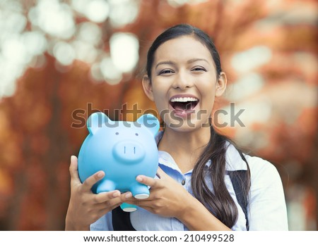 Closeup portrait happy, smiling business woman, bank employee holding piggy bank, isolated outdoors indian autumn background. Financial savings, banking concept. Positive emotions, face expressions - stock photo