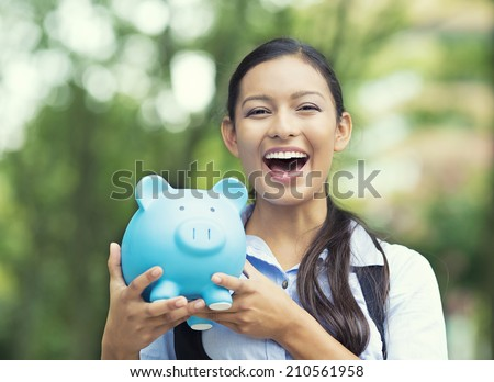 Closeup portrait happy, smiling business woman, bank employee holding piggy bank, isolated outdoors green trees background. Financial savings, banking concept. Positive emotions, face expressions - stock photo