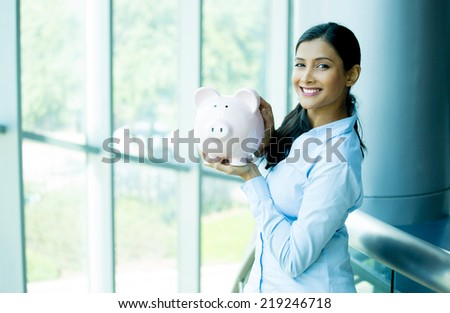Closeup portrait happy, smiling business woman, holding pink piggy bank, isolated indoors office background. Financial budget savings, smart investment concept - stock photo