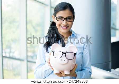 Closeup portrait happy, smiling business woman, holding pink piggy bank, wearing big black glasses isolated indoors office background. Financial budget savings, smart investment concept - stock photo