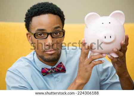 Closeup portrait happy, smiling businessman in black glasses and bowtie, holding pink piggy bank, isolated indoors office background. Financial budget savings, smart investment concept - stock photo