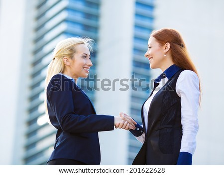 Closeup portrait happy smiling businesspeople, attractive business women shaking hands outdoor, isolated background corporate office, building background. Positive face expressions, emotions, attitude - stock photo