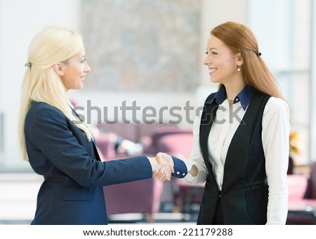 Closeup portrait happy smiling businesspeople, attractive business women shaking hands, standing in a hallway of corporate office. Positive human face expressions, emotions, attitude - stock photo