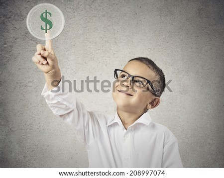 Closeup portrait happy, smiling child touching green dollar sign button on a touchscreen display, isolated  grey wall background. Positive face expression, emotions life perception. Financial concept - stock photo