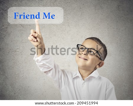 Closeup portrait happy, smiling child touching, pressing friend me button, icon on touchscreen display isolated grey background. Positive face expression, emotion life perception. Social media concept - stock photo