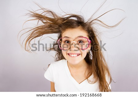 Closeup portrait happy, smiling , excited, funny looking, little girl with big glasses, messy hair, isolated dark blue background. Positive human emotion, facial expression, attitude, reaction - stock photo