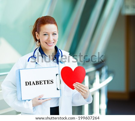 Closeup portrait happy smiling female health care professional, woman family doctor, cardiologist with stethoscope holding sign diabetes, heart isolated hospital hallway background. Patient plan - stock photo