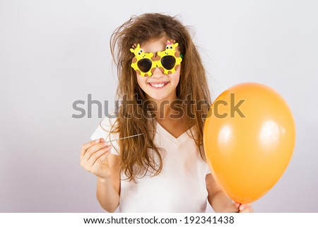 Closeup portrait happy, smiling, funny looking little girl with sunglasses, holding orange balloon and needle about to burst bubble, isolated background. Human face expressions, emotions, feelings - stock photo