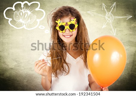 Closeup portrait happy, smiling, funny looking little girl with sunglasses, holding orange balloon and needle about to burst bubble isolated background with sun. Human face expression, emotion feeling - stock photo