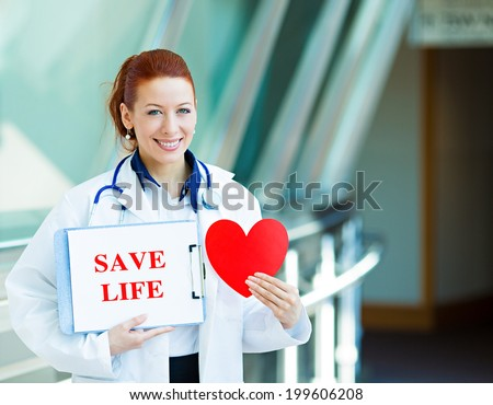 Closeup portrait happy smiling health care professional, woman transplantation medicine doctor, cardiologist with stethoscope holding sign save life, heart isolated hospital hallway background. - stock photo
